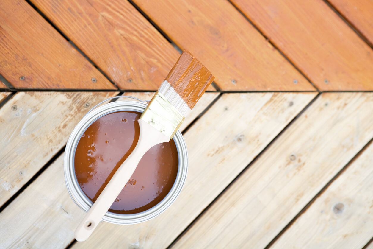 Staining decks- pail of stain and brush on half stained decking