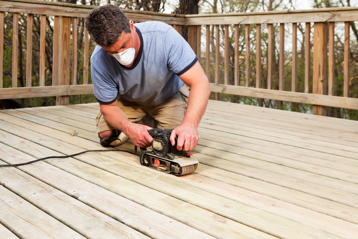 Man using electric sander on his clean deck