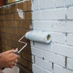 What You Need For Painting Or Staining Brick- painting on a fresh coat on brick wall