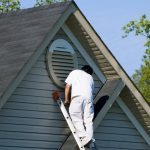 Professional painter painting the exterior of a home on a ladder