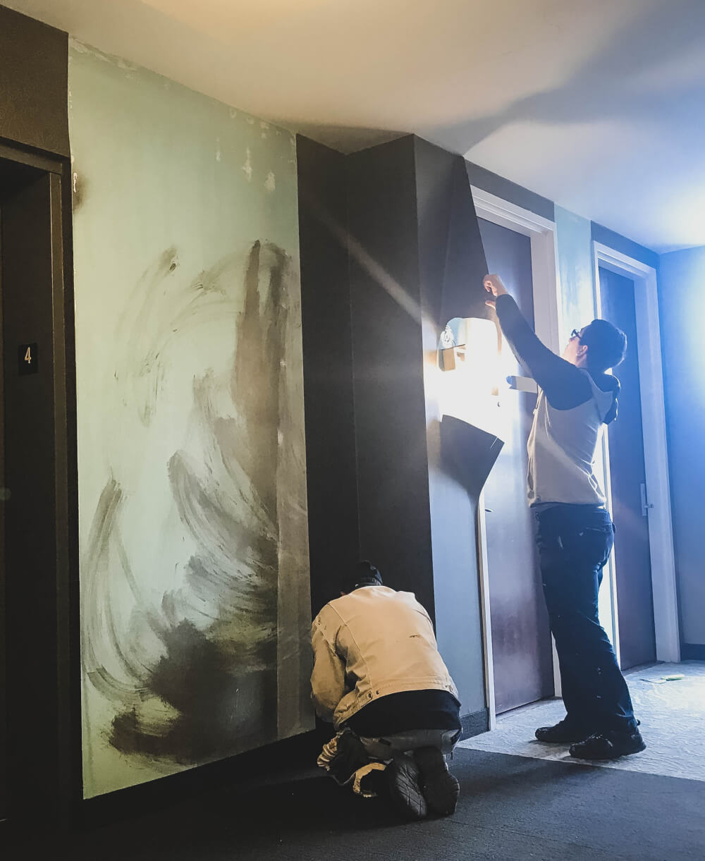 Professional wallpaper removal- two New Approach team members removing wallpaper from an elevator foyer