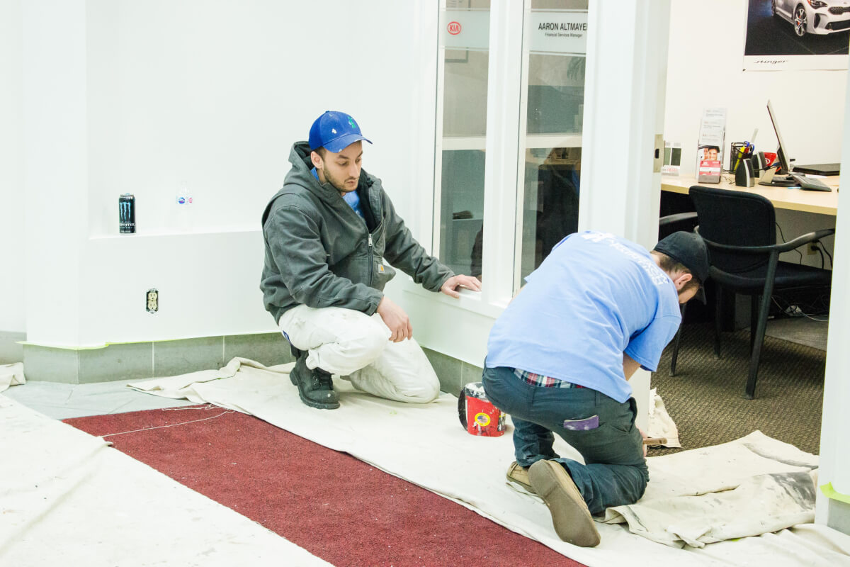 New Approach Painting Production Manager training a team member who is painting