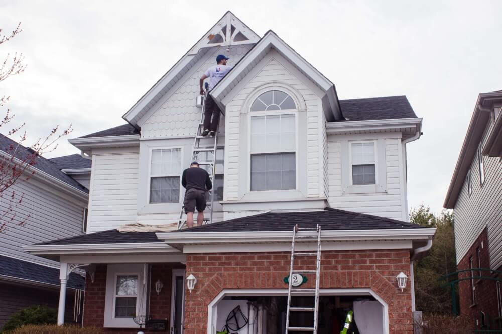 Painters painting the second floor exterior siding of a home
