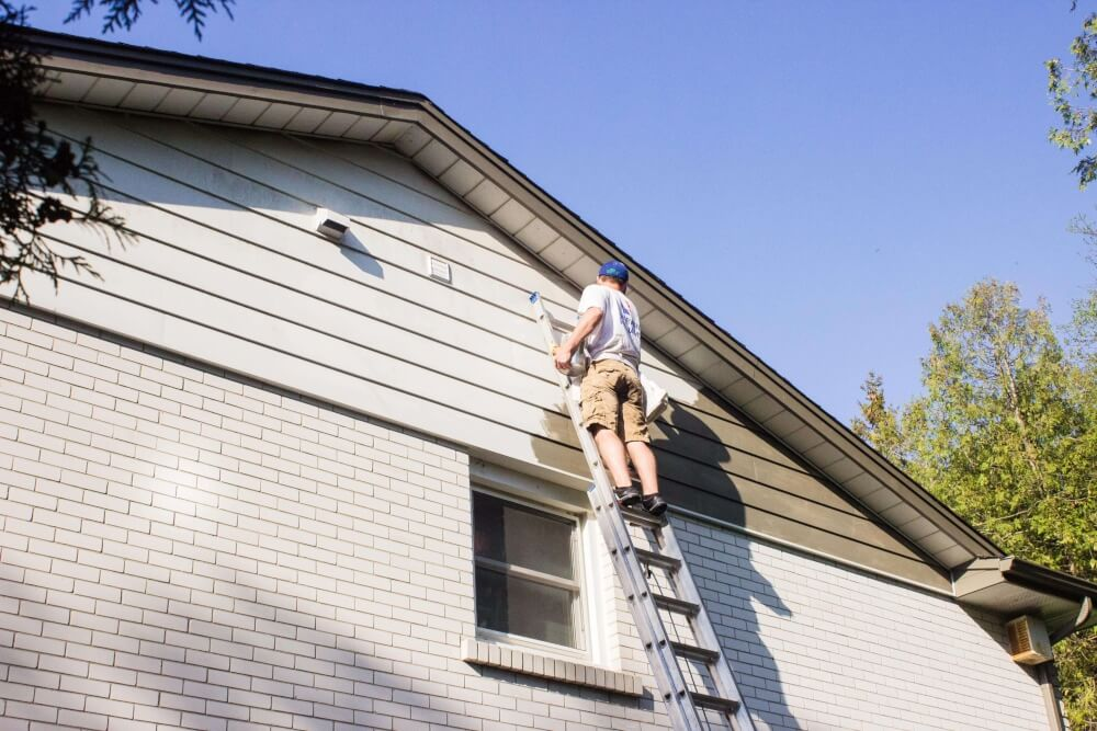 Painter painting exterior siding