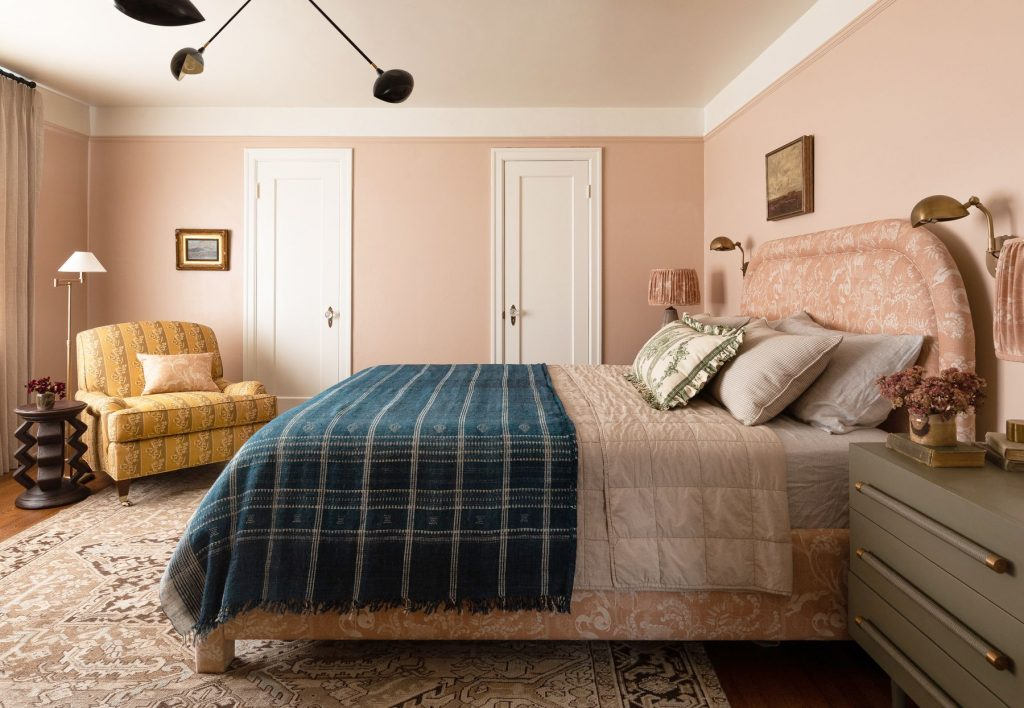 Pink walls in a bedroom with a white trim around the crown.